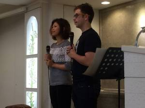 Angela sharing her testimony with Pastor Chris of Aroma translating